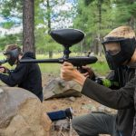 Two young men in masks aim their cheap paintball guns.