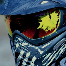 A man wearing dye paintball goggles