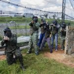 A group of young men are playing paintball with spyder paintball gear.