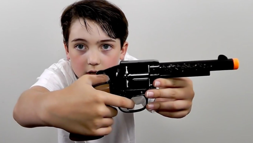 boy wearing white shirt holding toy gun